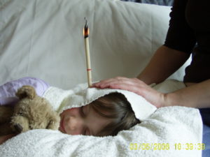 Child with an ear candle in their ear during a treatment session.
